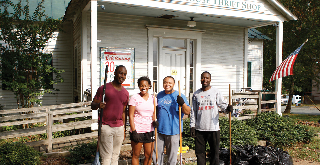 Black Law Students Association members and 2014 classmates Andrew Person, Andrea Canfield, Andrew Thebaud, and Sean Suber clean up outside the Schoolhouse Thrift Shop in Charlottesville as part of the organization's community service week in 2012.