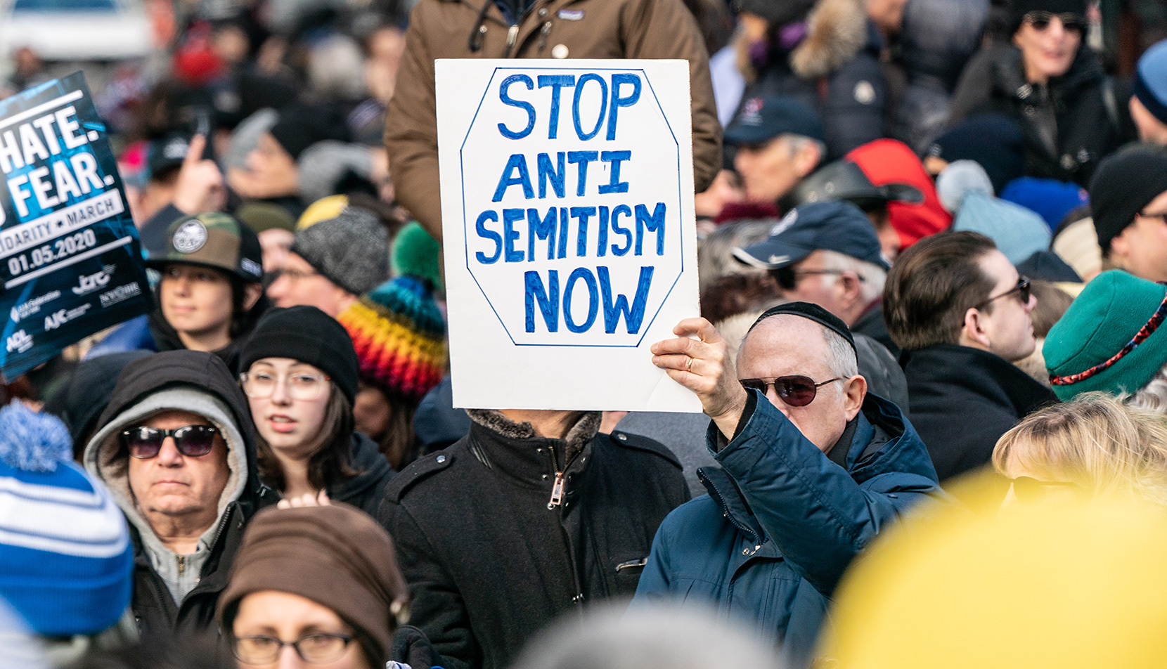 "Man holding ""Stop Anti-Semitism Now"" sign at protest"