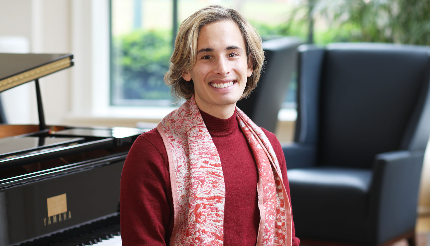 Christopher Benos sits at a piano