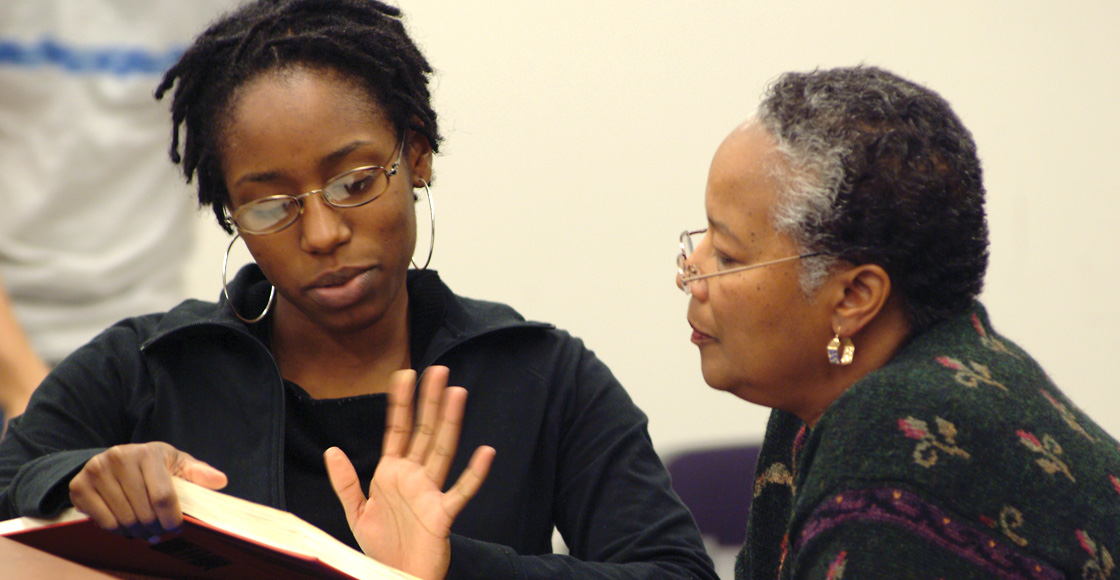 Professor Mildred Robinson talks with Gigi Parris '06  after class.