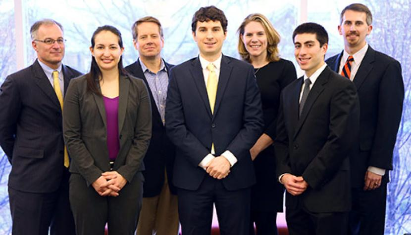 Pictured at the McGuireWoods law offices in Charlottesville, Partner Jonathan Blank '95, Lainie Singerman '16,  Partner Jim Neale '98, Justin Wilson '16, Associate Katherine Mims Crocker '12, Alex Cohen '15 and Associate Brian Schmalzbach '10 are among members of Arsean Hicks' legal team.