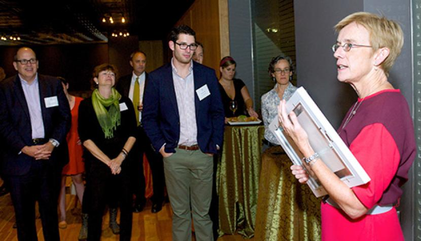 Anne Coughlin, right, receives the framed award as others in attendance look on.