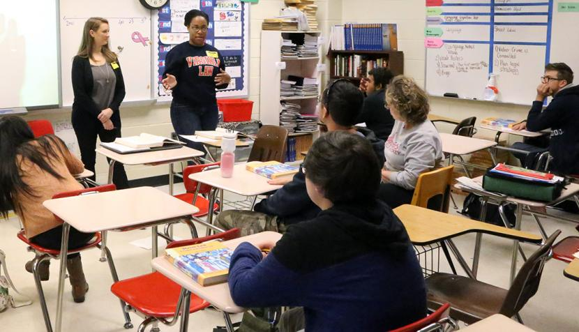 UVA Law students Arianna Lacerte and Jessica Douglas, standing, cover phases of a criminal trial with high school seniors in a government class at Albemarle High School.