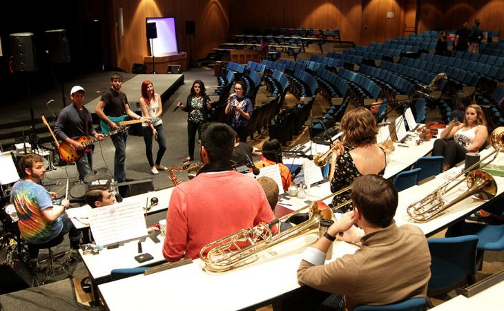 A student band warms up in Caplin Auditorium.