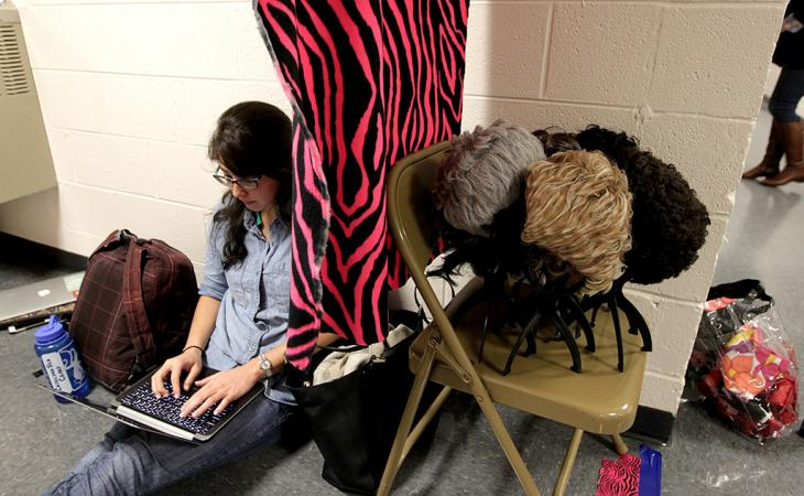 A student on her laptop next to a pile of wigs.