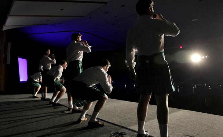 Students in kilts sing and dance on stage.
