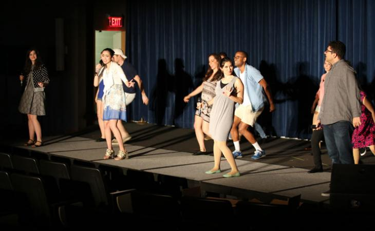 Lynden Unger '19, Genevieve Khuong '19, Mika Bray '19 and Robbie Pomeroy '19 perform in the foreground of a musical number.