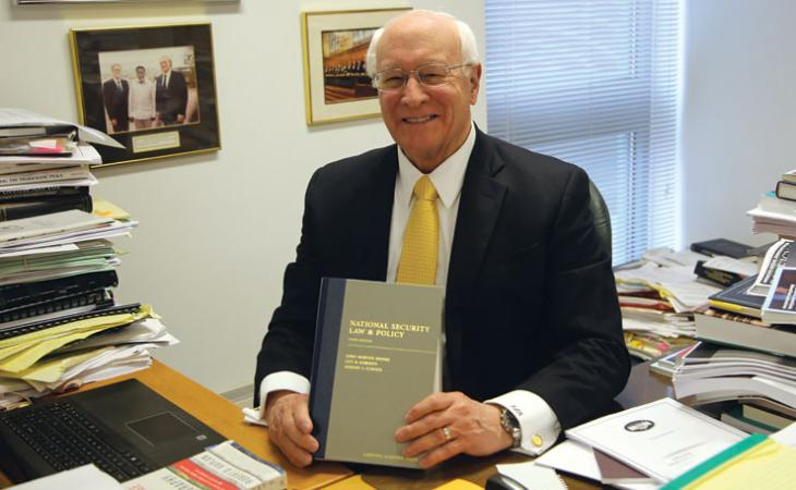 "Moore holds up his classic casebook, ""National Security Law."""
