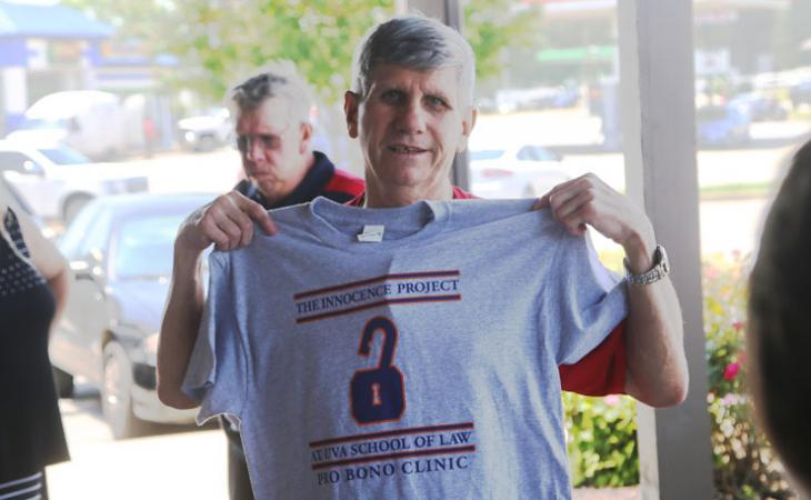 Emerson Stevens holds up an Innocence Project Pro Bono Clinic T-shirt.