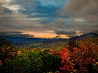 Photo of mountains with trees in autumn and clouds in the sky.
