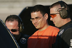 Jose Padilla, center, is escorted to a waiting police vechicle by federal marshals near downtown Miami in this Jan. 5, 2006, file photo. (AP Photo/J. Pat Carter)