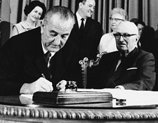 President Lyndon B. Johnson signing the Medicare Bill in Independence, Mo., on July 30, 1965, with honorary guest former President Harry S. Truman.
