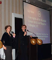 Professors Liz Magill (left) and Anne Coughlin help auction a vacation to a ski and golf