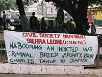 A sign calls for former Liberian president Charles Taylor to be indicted for war crimes.