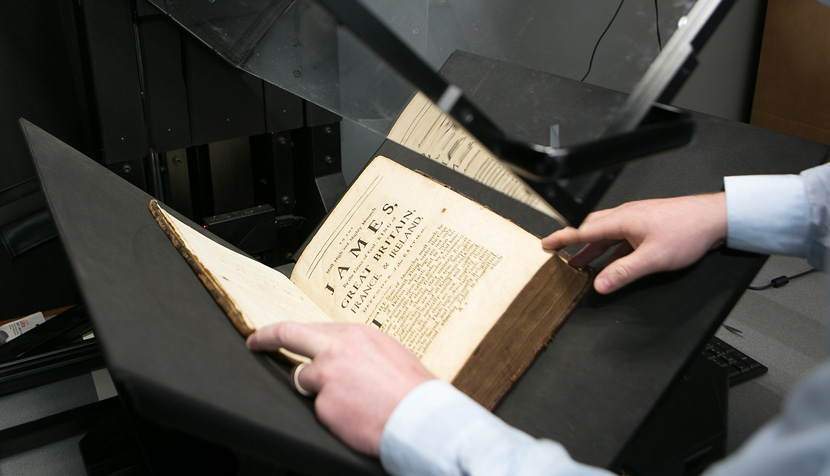 A book once owned by a Scottish lord, now owned by UVA as part of the collection it's compiling, is prepared for scanning.